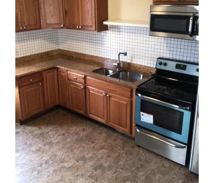 Clean kitchen with wooden cabinets and stainless steal appliances