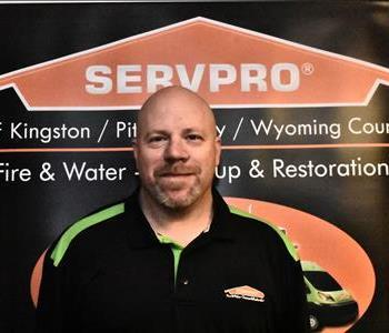 male employee in front of SERVPRO black and orange pop up sign