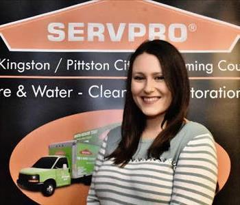Female Marketing Manager in front of SERVPRO black and orange pop up sign