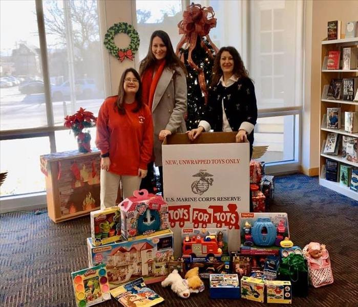 Three individuals in front of Christmas Tree with Toys for Tots box and toys in front of them