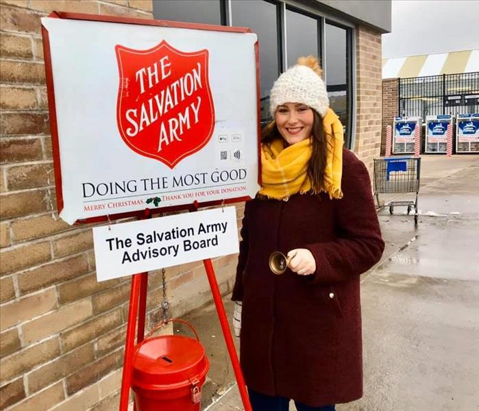 Woman ringing bell in front of Salvation Army Red Kettle and SignTaking some time the last two Wednesdays to volunteer