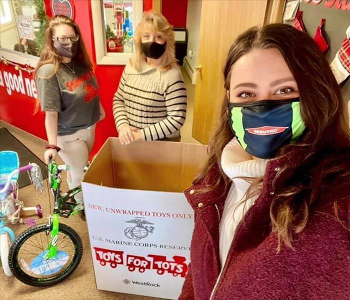 Three individuals with Toys for Tots box and bikes