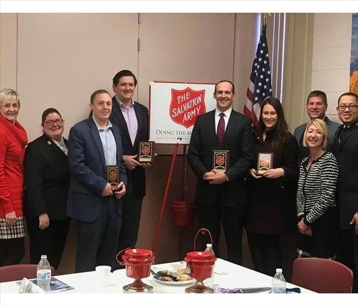 Salvation Army Advisory Board in front of Red Salvation Army Logo and Red Kettle