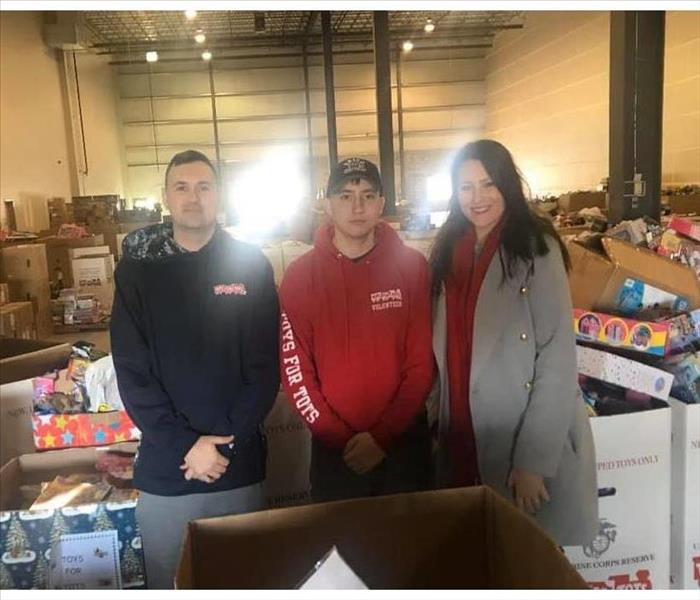Three individuals in Toys for Tots warehouse with Toys in boxes
