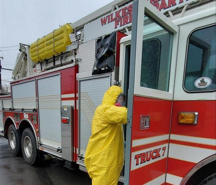 SERVPRO tech in yellow PPE cleaning red Wilkes-Barre Firetruck