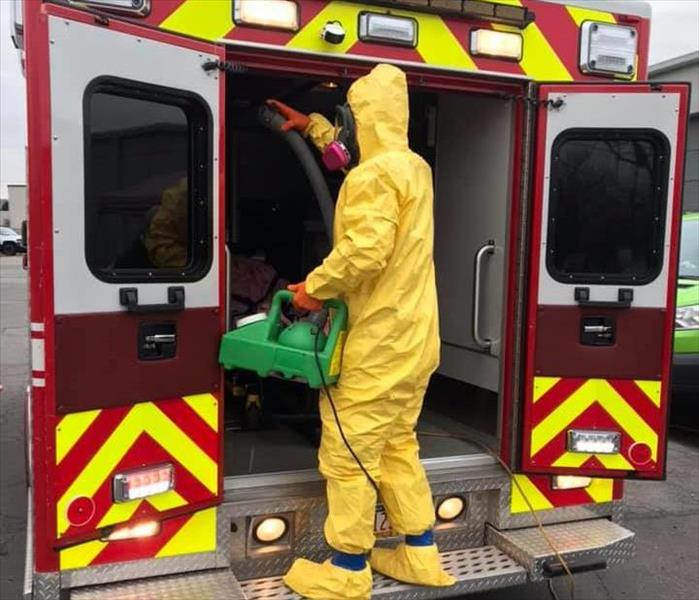 SERVPRO tech in yellow PPE cleaning red Kingston Ambulance