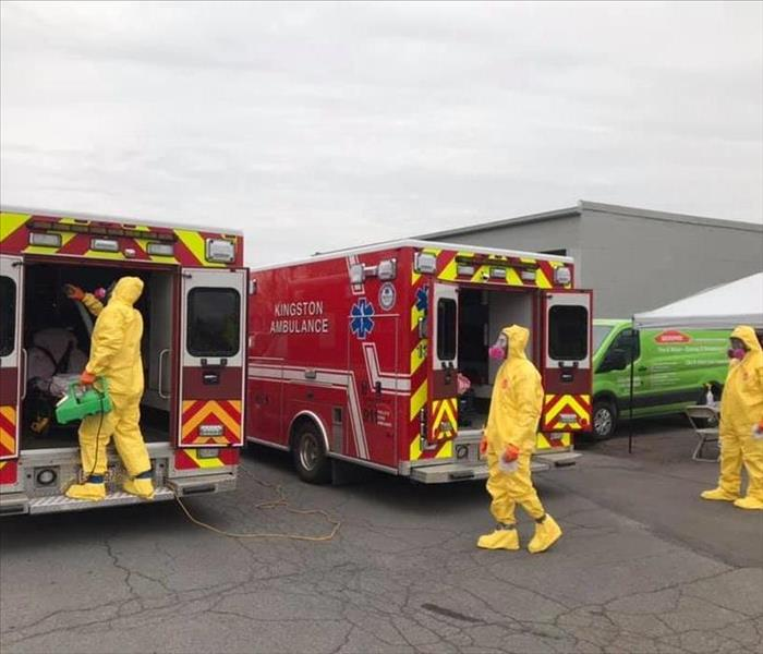 Three SERVPRO techs cleaning two red Kingston Ambulances