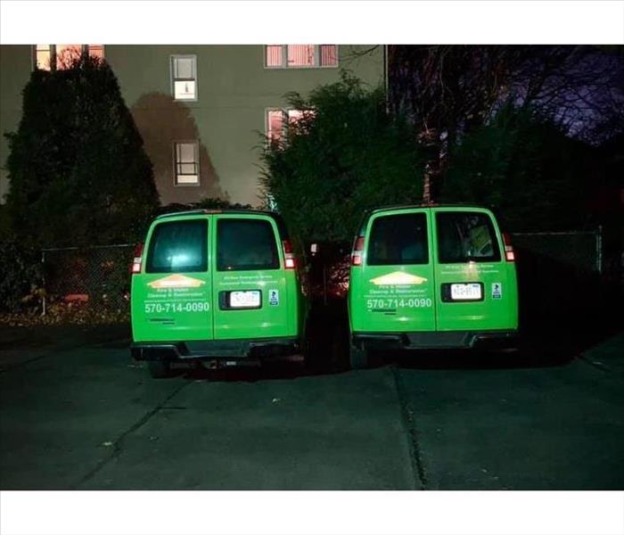 Two green SERVPRO Vans in parking lot at night time