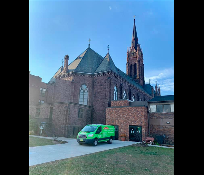 Green SERVPRO van in front of Church