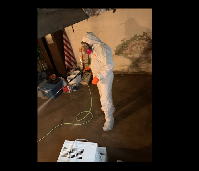 Technician dressed in white PPE in residential basement