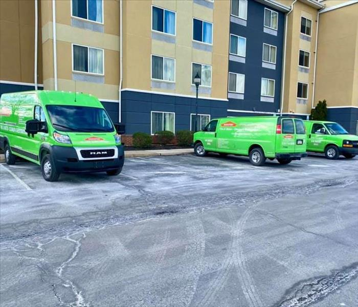 Three green SERVPRO trucks in front of hotel