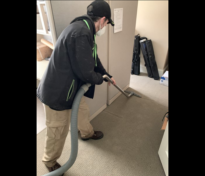 SERVPRO technician extracting water from light grey carpet
