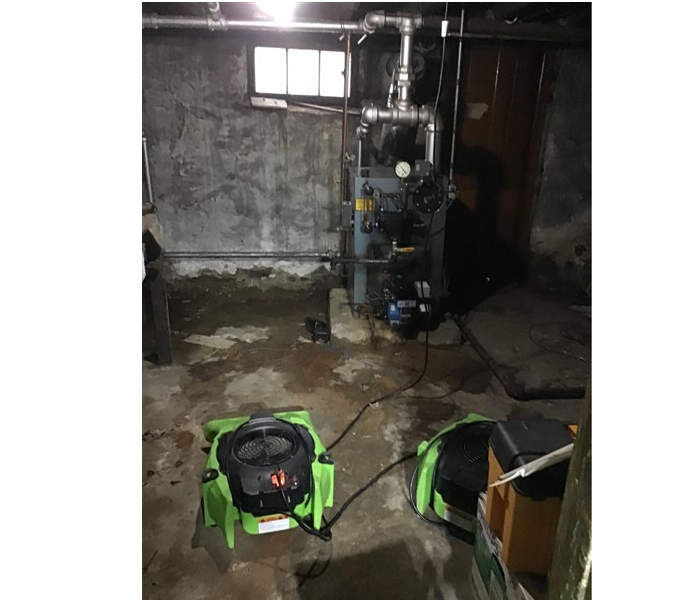 concrete basement with green SERVPRO fans drying out the water damage near the water heater