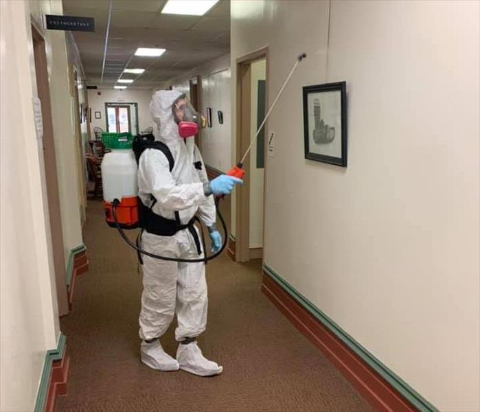 SERVPRO technician in white PPE with fogger