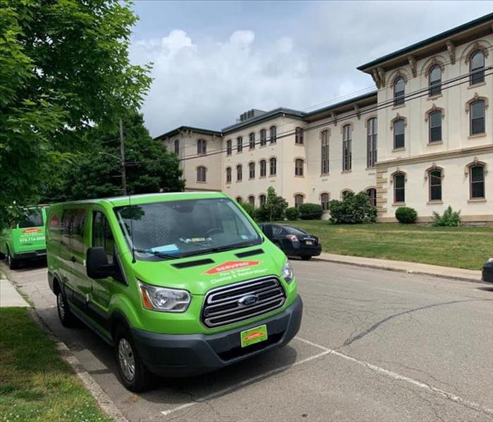 Green SERVPRO truck in front of large tan courthouse