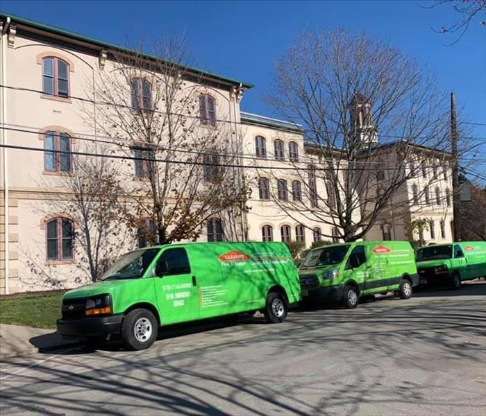 Three green SERVPRO trucks in front of commercial building