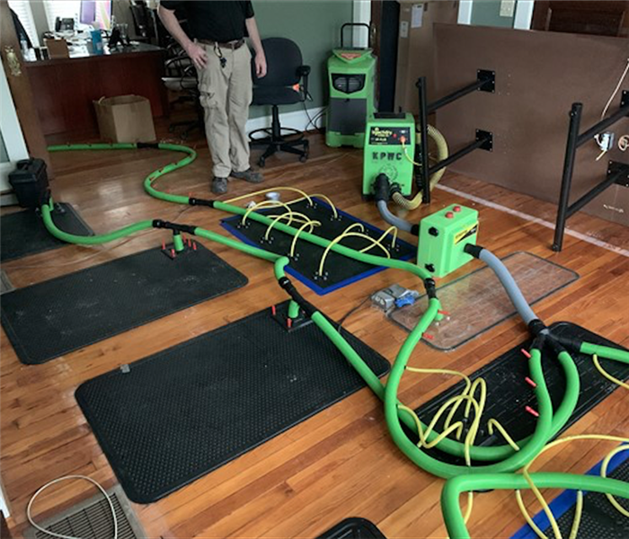 Green SERVPRO equipment on hardwood floors with black mats