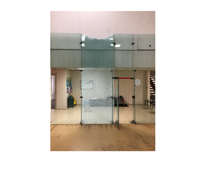 shattered glass doors in commercial building with wood floors