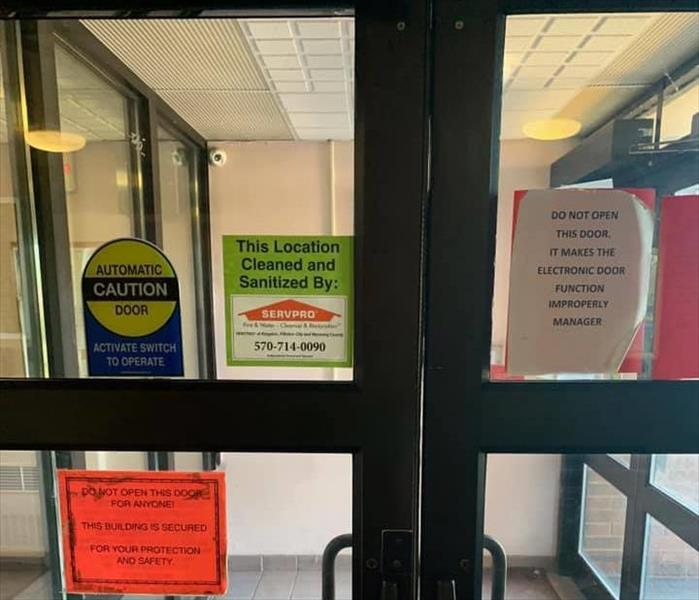 SERVPRO Cleaned and Sanitized sign on glass door to building