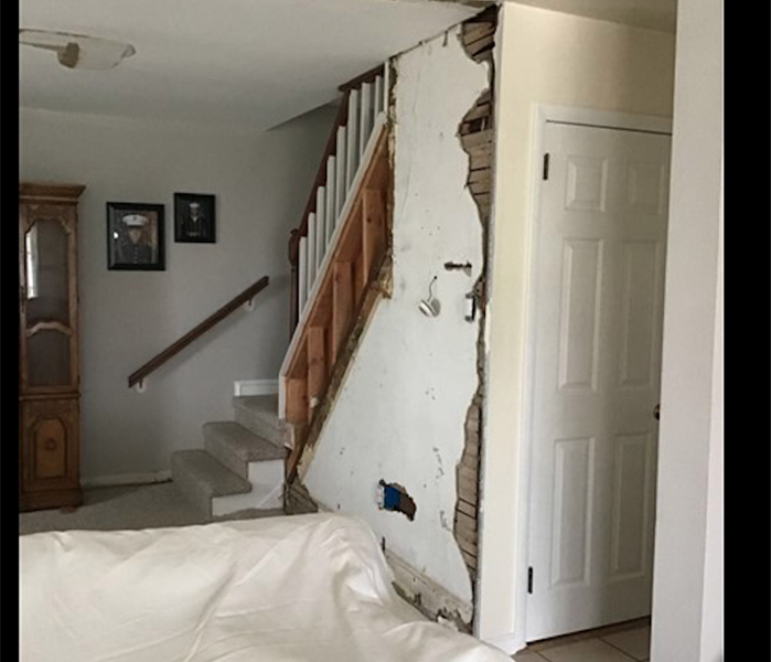 white wall near staircase with water damage