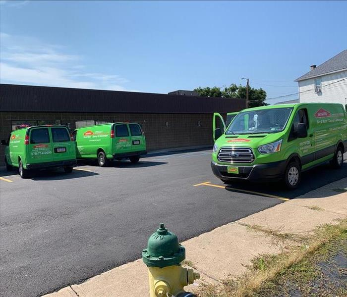 Three green SERVPRO trucks in parking lot of commercial building
