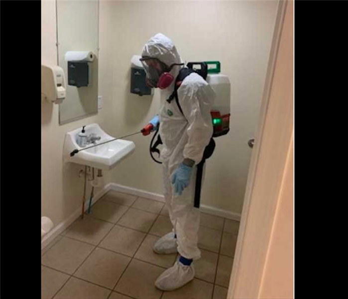 Technician in white PPE fogging restroom