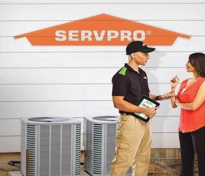 Technician speaking with homeowner in front of HVAC Unit and orange SERVPRO logo.