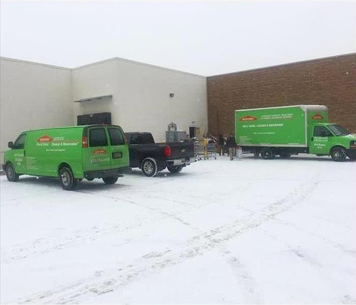 Green SERVPRO trucks outside commercial building in the snow