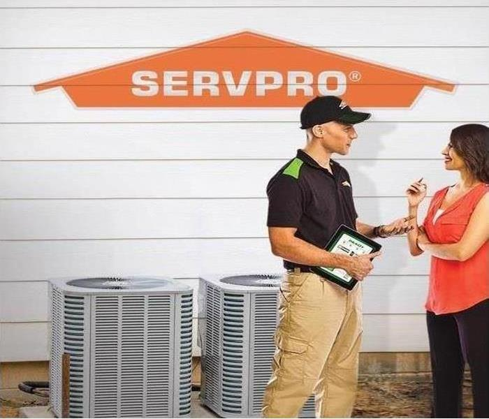 SERVPRO technician with homeowner in front of HVAC