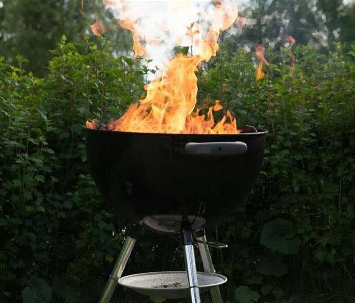 Black grill with flames and green trees in the back