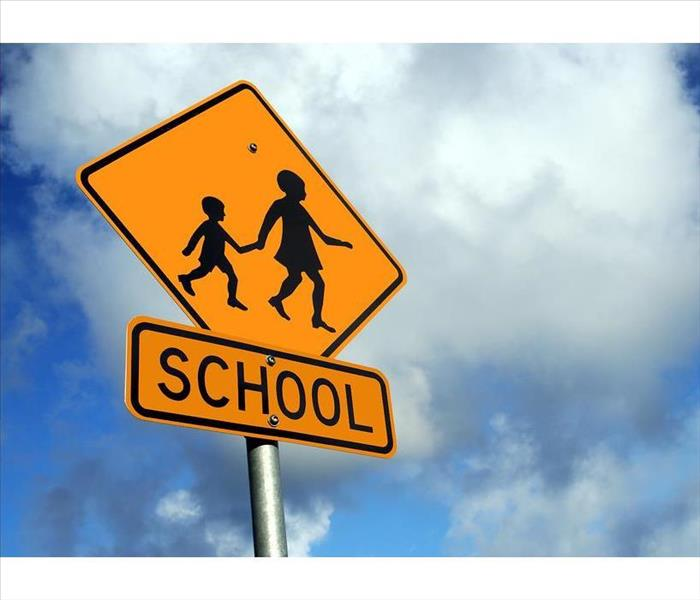 pedestrian/school crossing sign with blue sky background