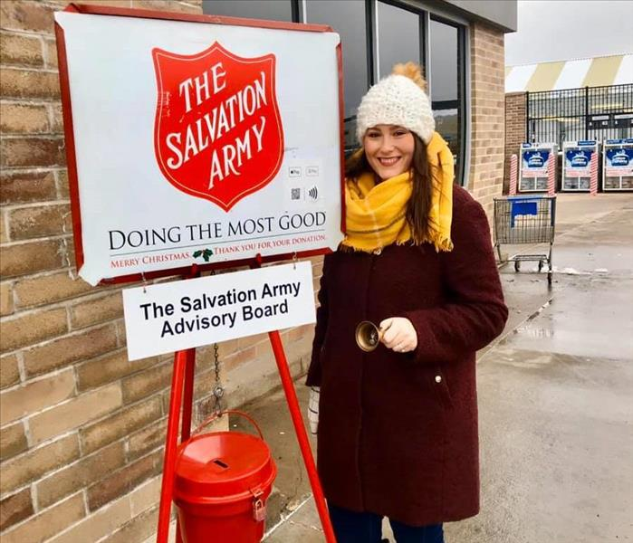 Woman in front of Salvation Army Advisory Board sign ringing bell